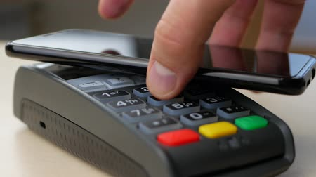 nfc : Making Nfc Payment By Mobile Phone with Digital Credit Card at Table. Finger entering the PIN code Stock Footage