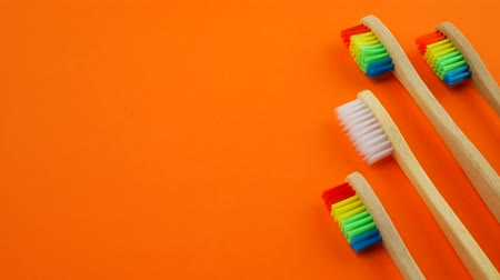 escova de dentes : White and rainbow wooden toothbrushes on orange background. Concept of racism, social exclusion, depression or loneliness, social problems or illegal migration