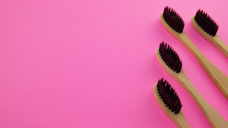 escova de dentes : Black wooden toothbrushes on pink background