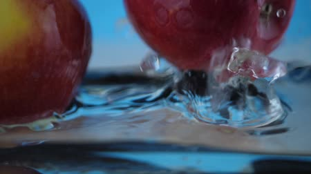 fejest ugrik : Red yellow apple under water with a trail of transparent bubbles at blue background. Slow motion water splashing concept