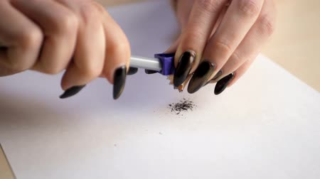 papeteria : Woman hands with dark manicure sharpening pencil and shavings on a white sheet of paper at office