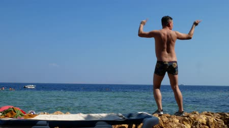 mestiça : Young crazy man dancing on beach with marine sea surface background