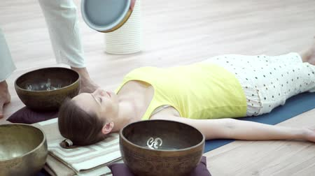 karma yoga : Young woman practicing yoga with singing bowl with wooden striker