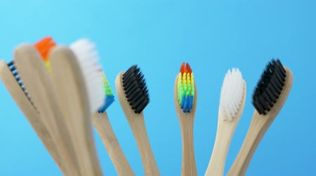 туалетные принадлежности : Colorful wooden toothbrushes in spinning cup on blue background. Dental hygiene and health conceptual