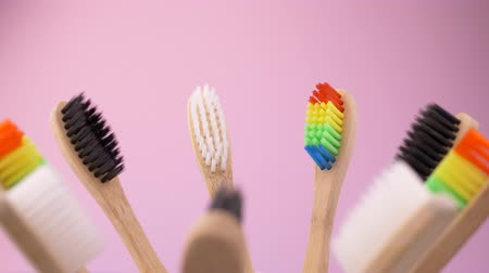 sanitário : Colorful wooden toothbrushes in spinning cup on pink background. Dental hygiene and health conceptual