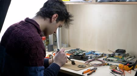 mühendislik : Repair of electronic devices, tin soldering parts in electronics workshop with PC matherboards background Stok Video