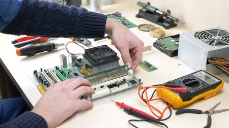 shops : Hand repairing computer and working with RAM memory on PC motherboard in electronics workshop