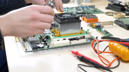 technikus : Young man installing CPU cooler fan on motherboard. Engineer assembling CPU in repair shop