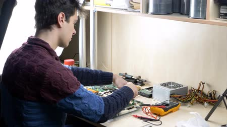 kaloryfer : Young man working with CPU cooler fan on green PC motherboard. Repairman fixing components in computer unit Wideo