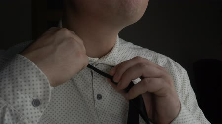 annoying : Tired businessman in white shirt untying his neck tie during late work in office Stock Footage