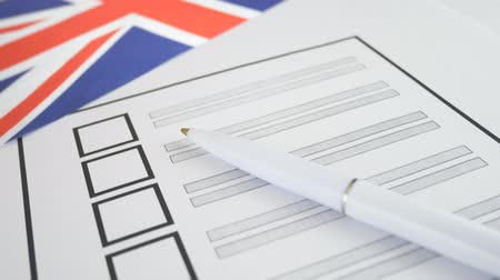 poll : White pen lying on voting ballot paper with vote checkbox place and England flag. Concept for voter registration and participation in elections in United Kingdom Stock Footage