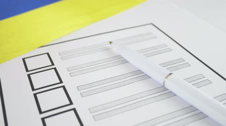 nástěnka : White pen lying on voting ballot paper with vote checkbox place and Ukrainian flag. Concept for voter registration and participation in elections in Ukraine