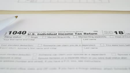 belasting invullen : Tax document for the IRS Income U.S. Individual 1040 Tax Return form on wooden table in office or at home Stockvideo