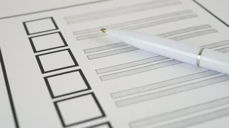 election : White pen lying on voting ballot paper with vote checkbox place. Concept for voter registration and participation in elections Stock Footage