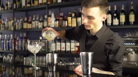 бурбон : Barman making alcoholic drink into the glasses with ice cubes on the bar counter