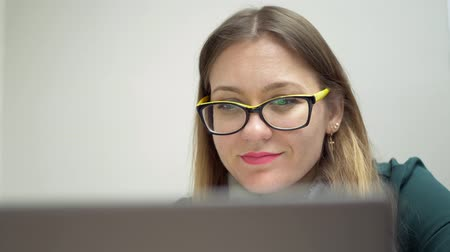 burocracia : English teacher in yellow glasses preparing for the lesson and working on laptop Stock Footage