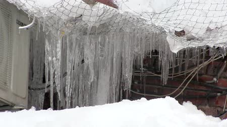 rampouch : Icicles hanging from a roof with air conditioning and safety net in winter day