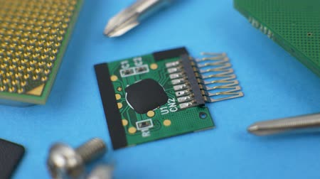 mikroişlemci : Electronic green circuit board with microchip and transistors on blue background with processor, screws and screwdriver Stok Video