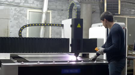 gravura : Engineer worker controls the cutting of metal plates on metal manufacture