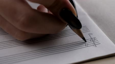 skladatel : Musician or composer hand writes a song or a musical work, writing notes with pencil on the pentagram