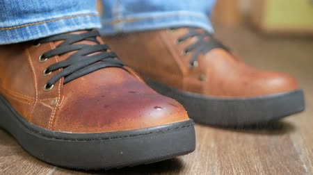süet : Hand dusting brown leather shoes with a yellow rag from dust and dirt. Autumn or winter shoes concept