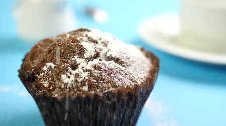geçiştirmek : Powdered or castor sugar falling down on chocolate cake or dessert on blue table with cup of coffee