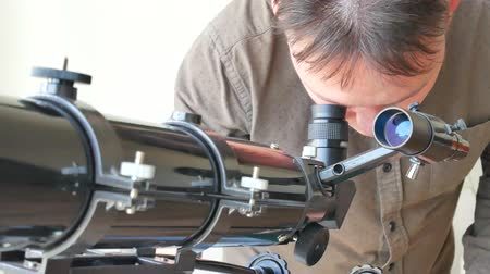 Man looking at the stars with telescope and writes data