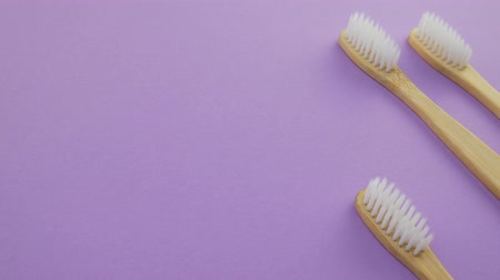 White and black bamboo toothbrushes on violet or purple background Dostupné videozáznamy