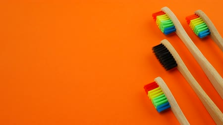 Black and rainbow bamboo toothbrushes on orange background Stok Video