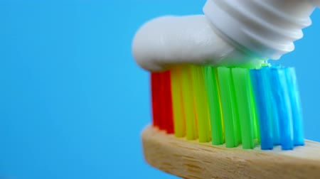 туалетные принадлежности : White toothpaste coming out of a tube on rainbow wooden brush at blue background
