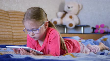 Little cute girl using tablet PC at home. Education and technology, children and people concept Stock mozgókép