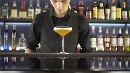 bourbon whisky : Barman making alcoholic drink into the glasses with ice cubes on the bar counter