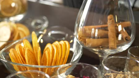 Spices, cinnamon sticks and dried orange fruits slices for making alcoholic drink on bar counter in restaurant or night club Stock mozgókép