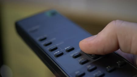 Hand presses button on black remote control television