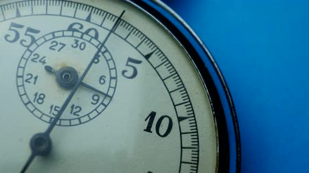 Analogue metal stopwatch on the blue background. Time start with old steel chronometer