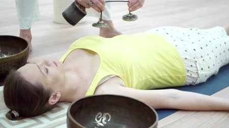 Woman practicing yoga meditation with tibetan singing bowl