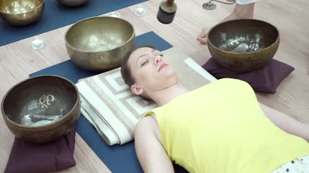 gong : Young woman practicing yoga. Shavasana or corps pose is the end of a class or practice Stock Footage
