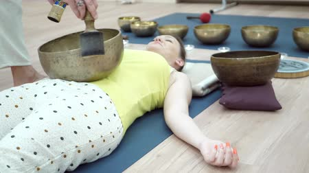 Young sporty woman practicing yoga lesson with instructor in gym, lying in dead body exercise, doing shavasana. Tibetan singing bowl meditation concept