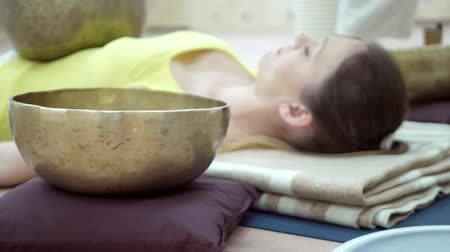 gong : Woman practicing yoga meditation with tibetan singing bowl