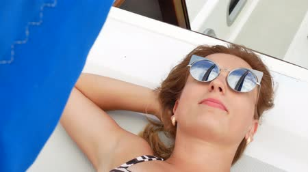 Pretty beautiful girl with light brown hair and wearing sunglasses lies on deck of white luxury yacht in swimsuit. Sunbathing at sunday in summer traveling by sea during voyage or cruise