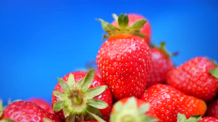 Fresh strawberries in a bowl at blue background Stok Video