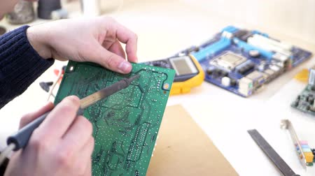 полупроводник : Young computer technician soldering green motherboard in electronics workshop