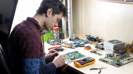 トランジスタ : Computer engineer with tester examining green motherboard with processor, chips and capacitors 動画素材
