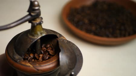 grãos de café : Hand of Barista Grinding Coffee Beans on Vintage Coffee Grinder on Table