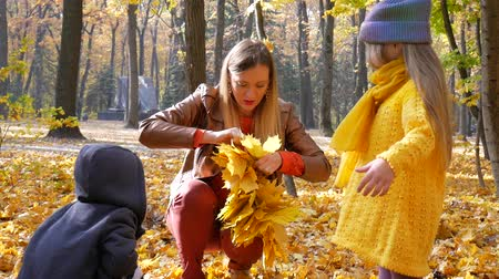 çelenk : Mother knits a yellow leaf wreath together with two children at park in autumn with colorful leaves and trees background