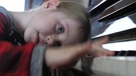 ziewanie : Girl of five years tired of learning the piano. Boring and tiresome music lesson at home. Wearisome homework