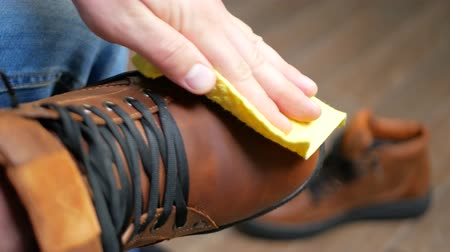 cipőfűző : Hand dusting brown leather shoes with a yellow rag from dust and dirt