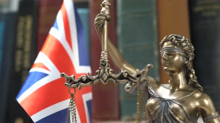veredito : Statue of Lady Justice with Bookshelf with Books and United Kingdom Flag Background. Tribunal and justice concept. Consultation with insurance lawyer and customer Vídeos