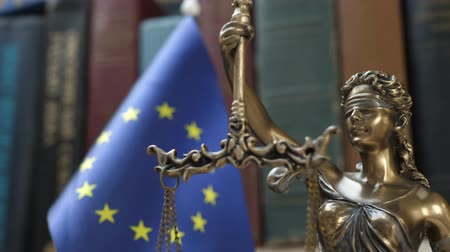 veredito : Statue of Lady Justice with Bookshelf with Books and European Union Flag Background. Tribunal and justice concept. Consultation with insurance lawyer and customer