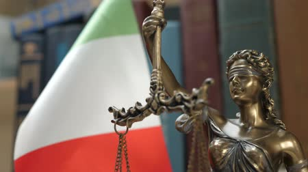 veredito : Statue of Lady Justice with Bookshelf with Books and Italy Flag Background. Tribunal and justice concept. Consultation with insurance lawyer and customer